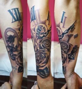 Tatuaje de mecanismo de reloj con rosas negras en el brazo