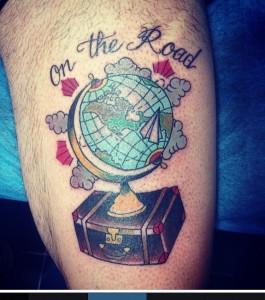 """Tatuaje de una bola del mundo sobre una maleta con el mensaje de """"On the road"""""""
