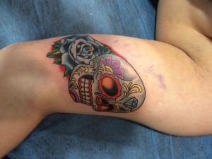 Tatuaje de una calavera y una flor ealizado en el brazo en nuestra tienda de Madrid