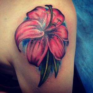 Tatuaje de flor roja en hombro realizada en nuestro centro de Montera - Madrid
