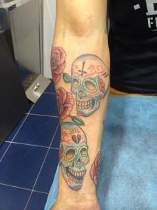 Tatuaje en brazo de varias calaveras azules y rosas