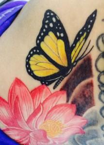 Tatuaje de mariposa amarilla con flor roja