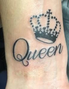 Detalle de tatuaje de corona de reina y palabra Queen en muñeca