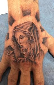 Tatuaje de rostro de la Virgen en mano