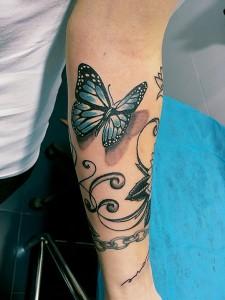 Tatuaje de mariposa azul volando en brazo