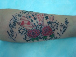 Tatuaje en brazo de cartas de la baraja francesa y rosas