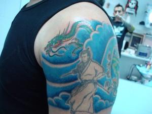 Tatuaje en brazo de un dragón y un guerrero chino