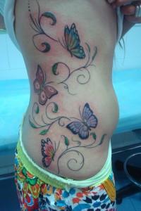 Tatuaje de flores en enredadera con mariposas en el costado