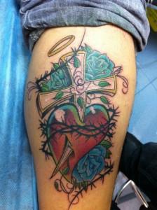 Tatuaje de cruz atravesando un corazón