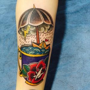 Tatuaje de taza en la que hay un barco navegando