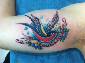 Tatuaje de golondrina en brazo