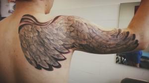 Tatuaje de ala recorriendo brazo