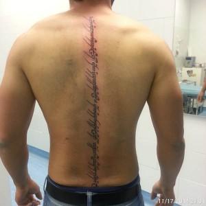Tatuaje de lettering recorriendo espalda