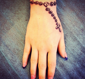 Tatuaje de rosario en muñeca