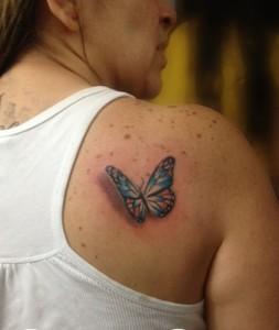 Tatuaje de mariposa azul en espalda