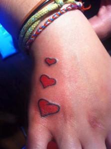 Tatuaje de tres corazones en mano