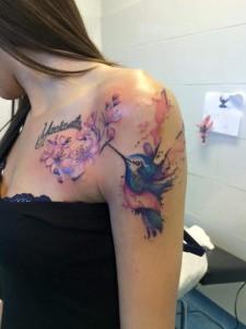 Tatuaje de colibrí y flores