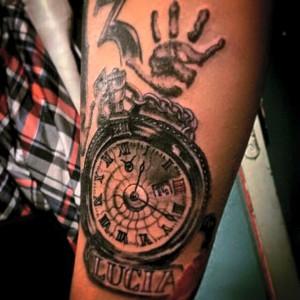 Tatuaje de reloj, mano y nombre de Lucía