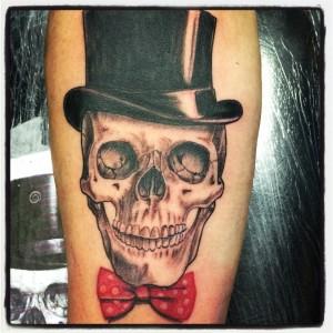 Tatuaje de calavera con chistera y pajarita