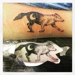 Tatuaje de lobo con luna en el costado