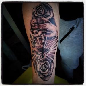 Tatuaje de mano con rosario y rosas negras