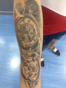 Tatuaje de reloj y rosa en brazo