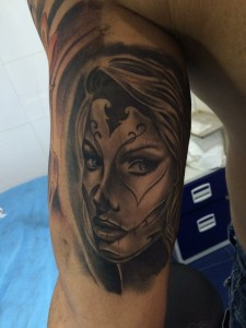 Tatuaje de rostro de mujer en brazo