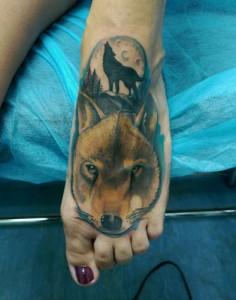 Tatuaje de cabeza de lobo en empeine del pie