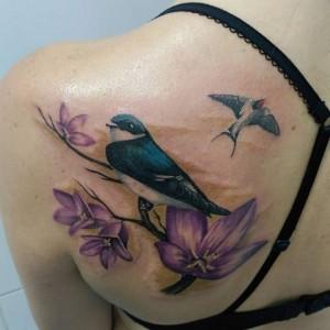 Tatuaje de pájaros sobre flores en la espalda