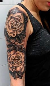 Tatuaje de rosas negras recorriendo el brazo