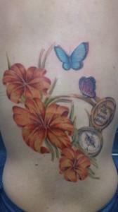 Tatuaje de flores naranjas, mariposas y brújula