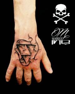 Tatuaje de triángulos invertidos en mano