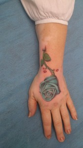 Tatuaje de rosa azul en mano