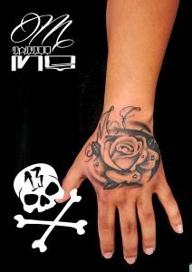 Tatuaje de rosa en negro en mano