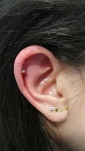Piercing en oreja con pendiente de ópalo