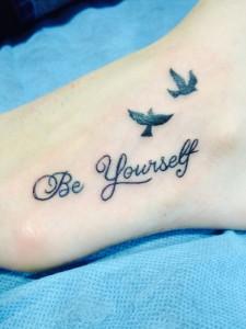 "Tatuaje de pájaros volando con frase ""Be yourself"""