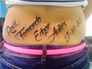 Tatuaje letterring con varios nombre en zona lumbar