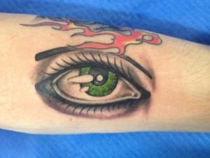 Tatuaje de ojo verde en brazo