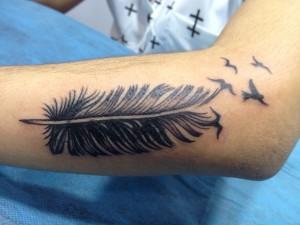 Tatuaje de pluma convirtiéndose en pájaros