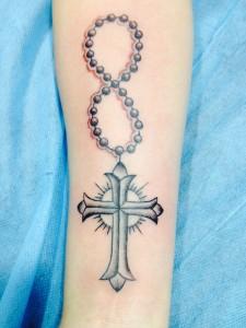 Tatuaje de rosario y cruz