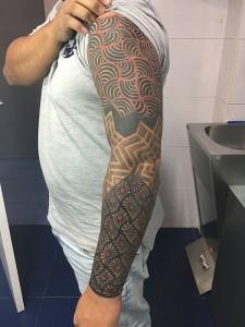 Tatuaje de elementos geométricos en brazo