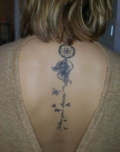Tatuaje de atrapasueños y lettering en la espalda