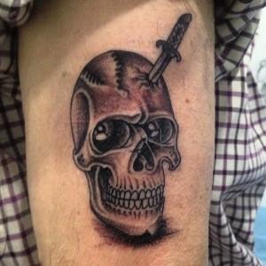 Tatuaje de calavera con puñal calvado