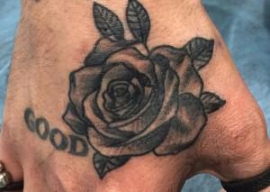 Tatuaje de rosa negra en mano