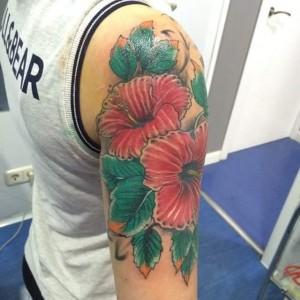 Tatuaje de flores rojas y verdes