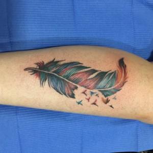 Tatuaje en color de pluma y pájaros