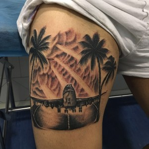 Tatuaje de avión despegando en pista con palmeras