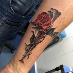 Tatuaje de rosa con espinas y cruz en brazo
