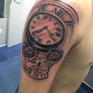 Tatuaje de reloj y nombres en brazo