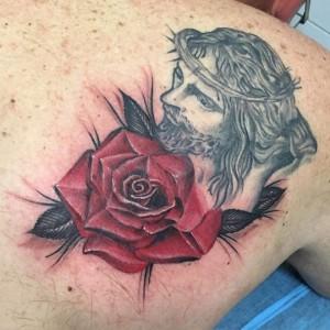 Tatuaje de cara de Cristo y rosa roja